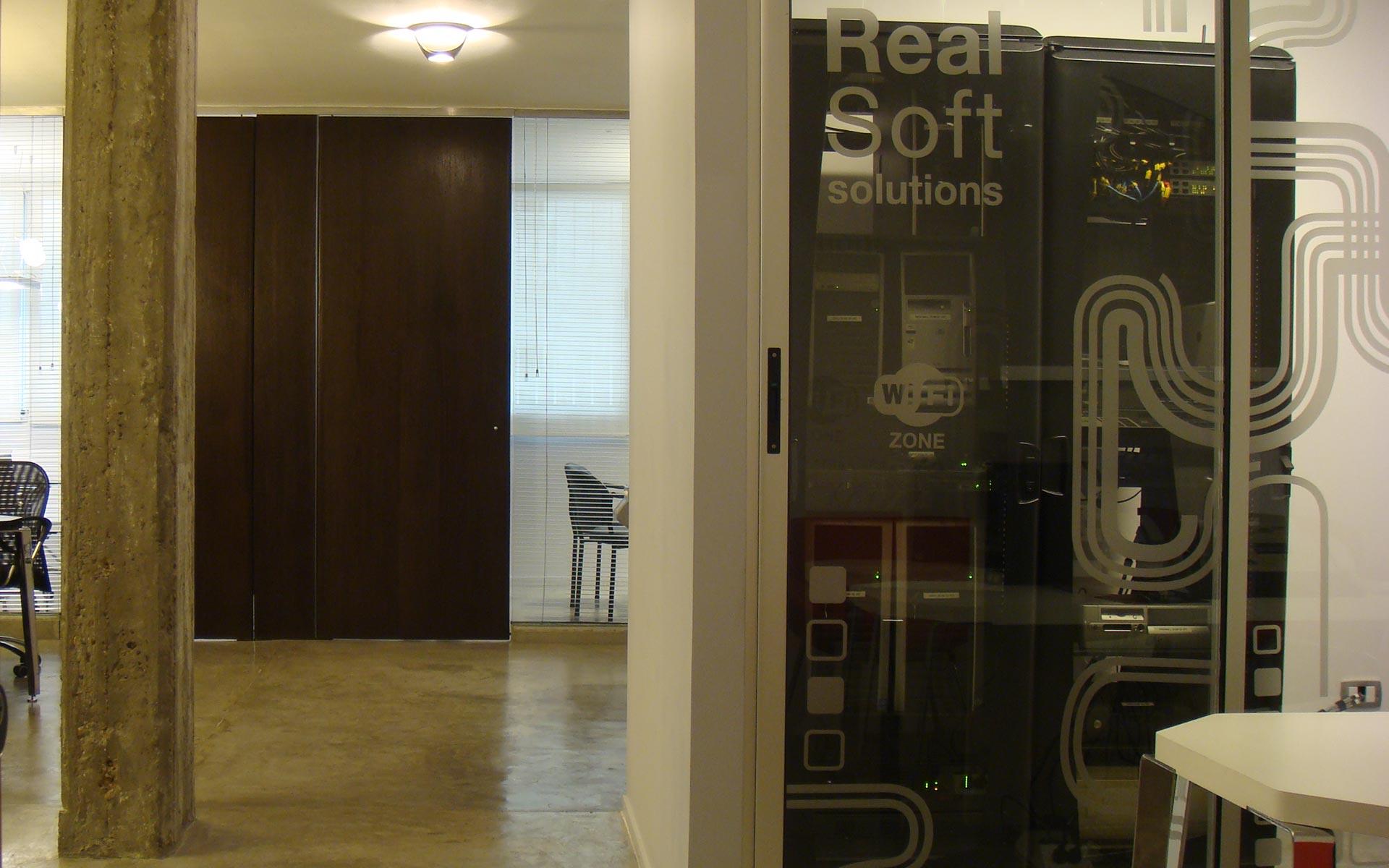 diseño interior, reforma oficina, sala general, columna de hormigón visto y piso de microcemento, puertas de madera oscura y paneles de vidrio