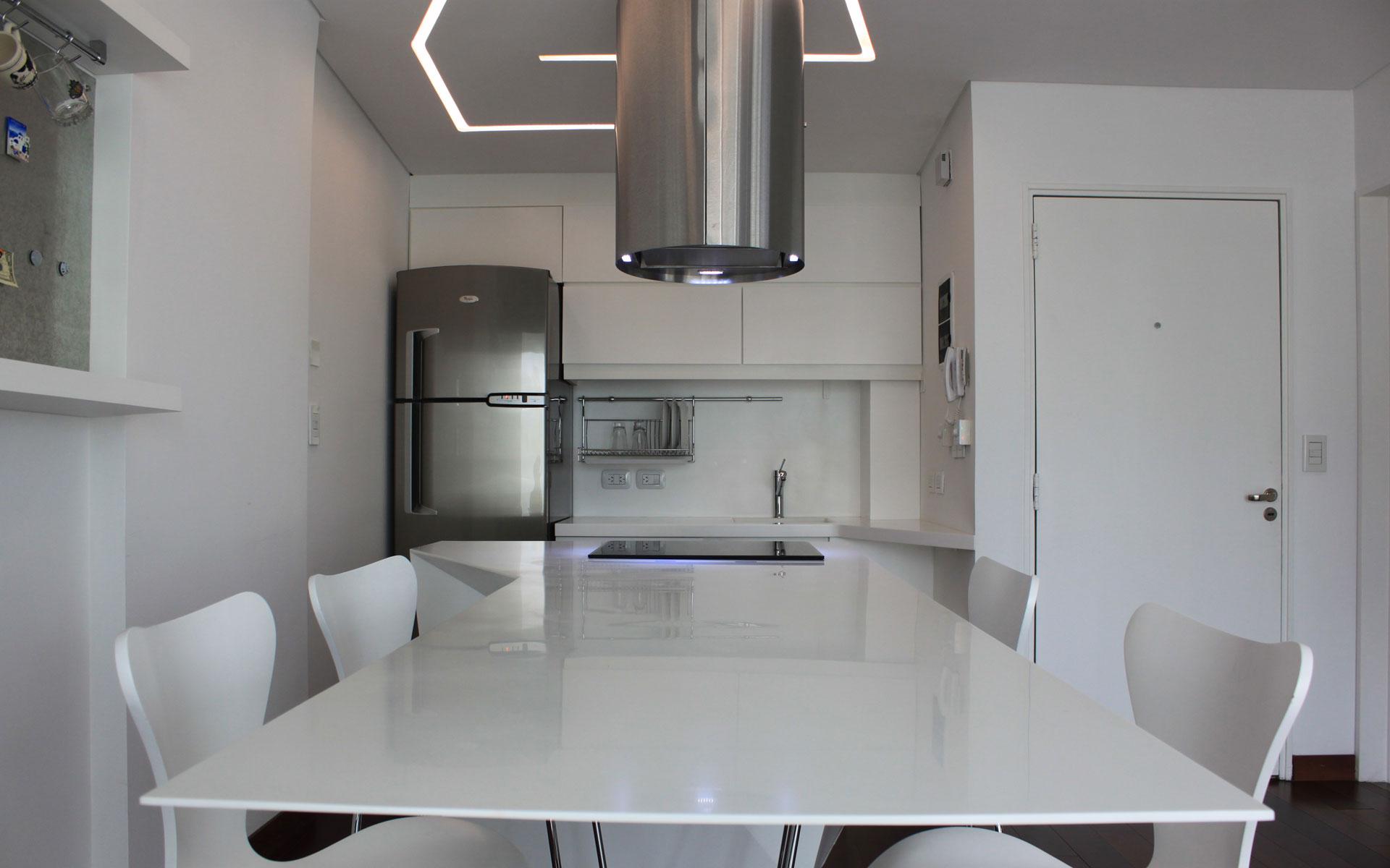 Diseño interior, cocina flotante mesada de corian blanco e iluminación custom made, campana cilíndrica y sillas butterfly blancas