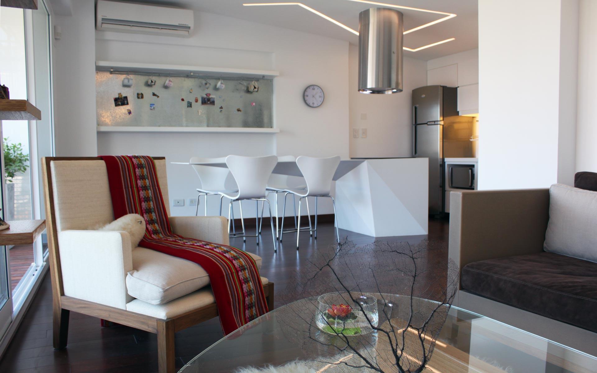 Reforma de departamento y deco, Isla de cocina con mesada flotante en corian blanco, sillas butterfly blancas, sofa gris el departamento reformado a nuevo