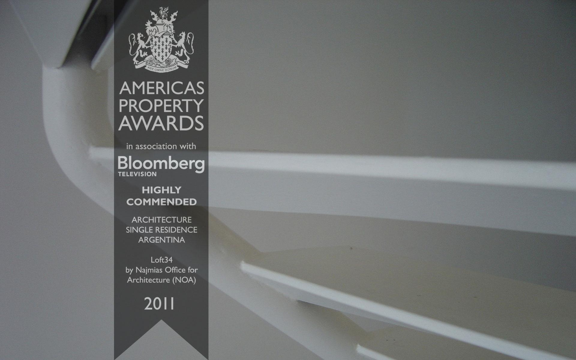 Foto de escalera flotante blanca del Loft34 con el logo de Najmias Oficina de Arquitectura ganador del Premio Americas Property Awards