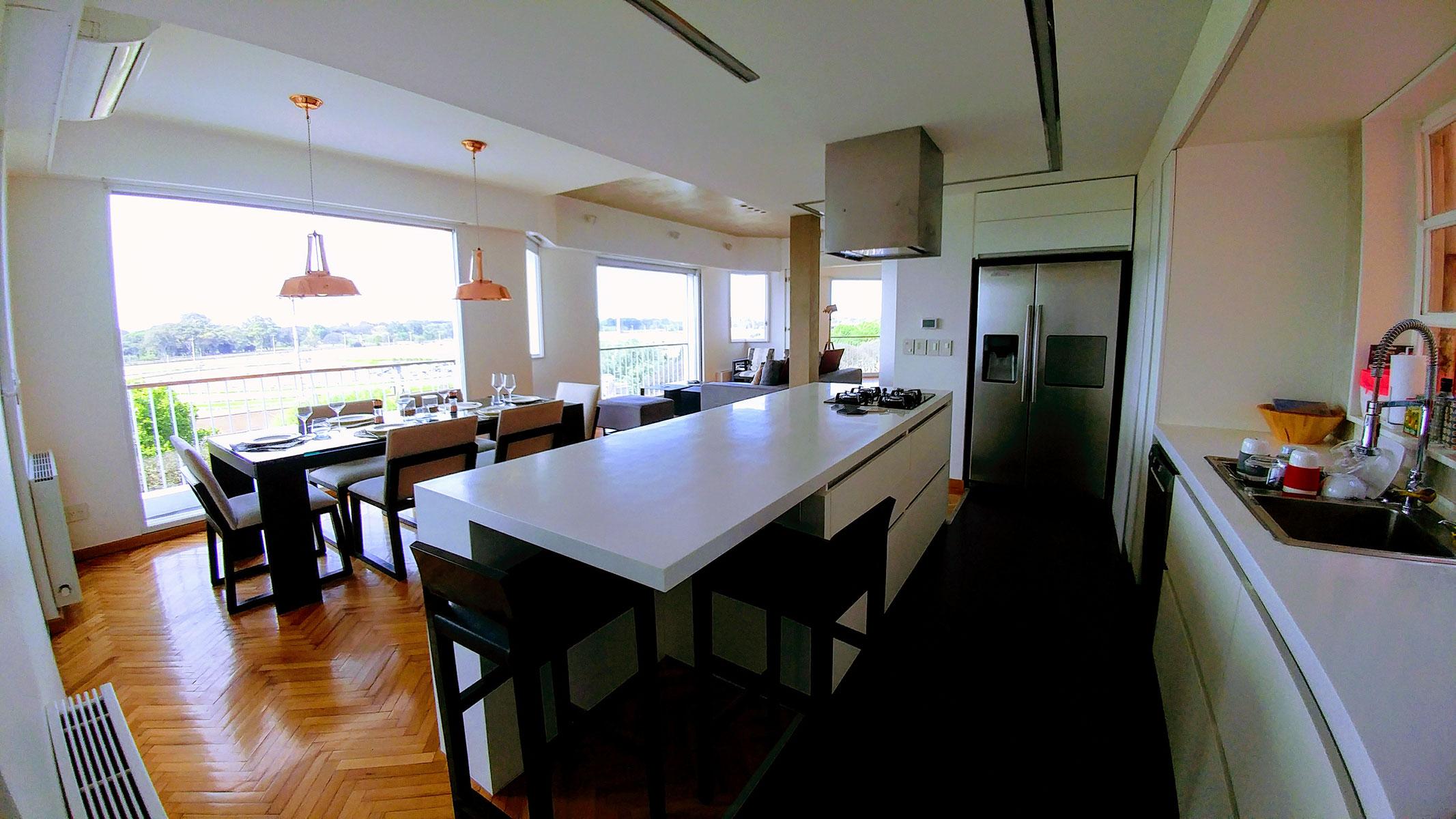 Diseño interior y reforma de arquitectura, cocina abierta, integrada o americana, en corian blanco, detalles en acero inox y lamparas de cobre